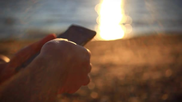 mans hands uses mobile smartphone near the sea at sunset beach. With blurred reflected In water background