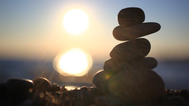 Stones pyramid on beach symbolizing zen, harmony, balance. Blurred Sea at sunset with bokeh background and reflected sun in water. Sound of the Sea