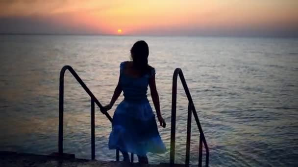 Silhouette of sexy woman climb stairs from the sea in dress, fashion model posing in sunset light, luxury summer vacation concept.