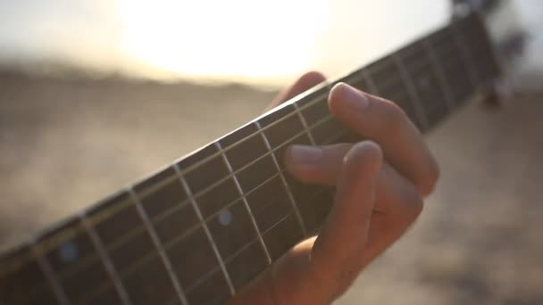 Fingers musician playing guitar in the beach during sunset on blurred background and sunlight in sea