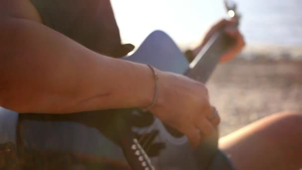 Musician hand playing guitar in the beach during sunset on blurred background and sunlight in sea