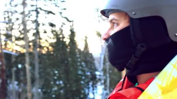 Mann mit Helm auf einem Berg auf einem Lift mit einem Snowboard auf einem Hintergrund von Bäumen, Bergen und Sonne
