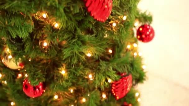 Karácsonyi dekoráció lógó lámpák, holly gallyak. díszek karácsonyi vásár alatt értékesítik. Homályos az emberek vásárlás a szupermarketben, a háttérben a bokeh