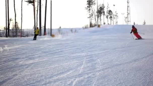 Pasažér lyžaři ubírá sníh prášku při západu slunce
