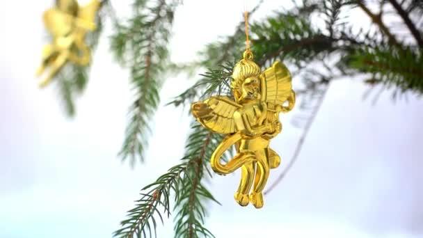 Vánoční dekorace s zlaté andílky na větvi smrku