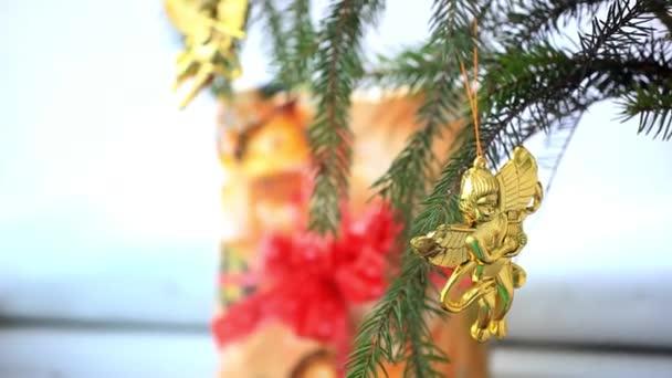 Vánoční dekorace s zlaté andílky na větvi smrku a dárek