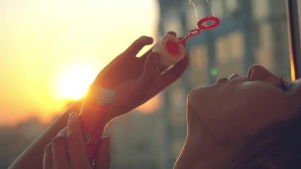 Lassú mozgás, mosolyog fiatal szép boldog nő fújt buborék: naplemente city