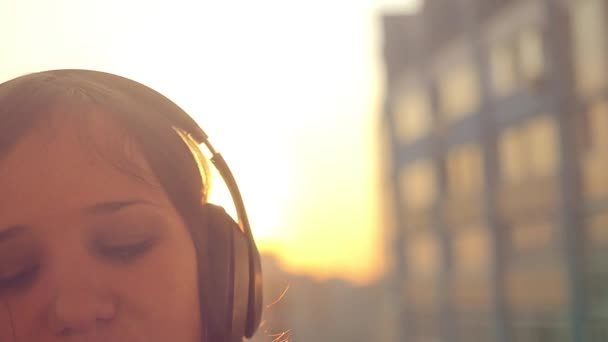 Slow motion of Young woman listening to music in headphones at city sunset and seductive paints her lips with lipstick,