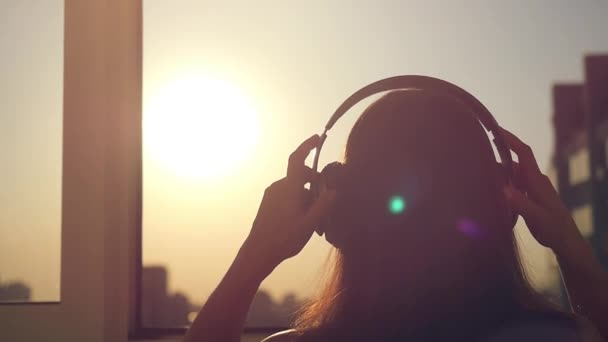 Slow motion of Young woman get dressed headphones, listening to music, dancing and looking at city sunset