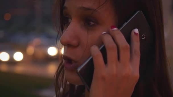 Businesswoman talking by mobile phone in city at night