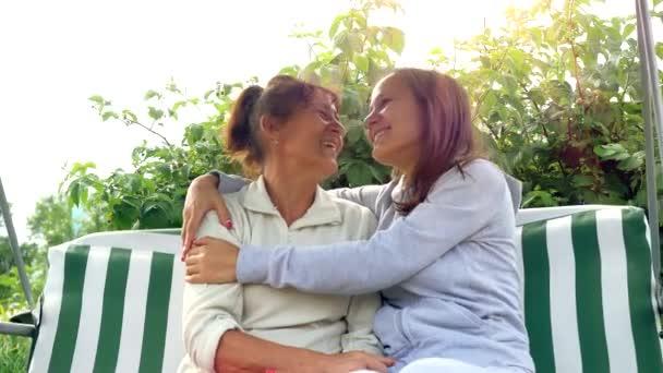 Lächeln Mutter und Tochter haben Spaß im Garten auf der Schaukel bei Sonneneinstrahlung