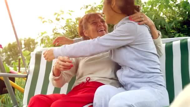 Mutter und Tochter amüsieren sich im Garten auf der Schaukel bei Sonneneinstrahlung