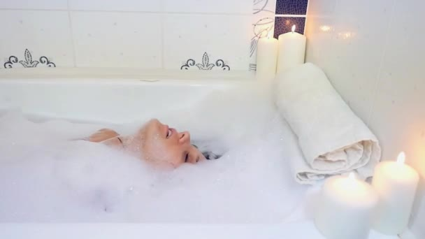 Beautiful young woman washing her hair in bathtub with foam