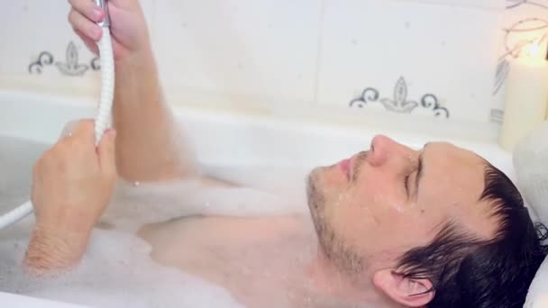 Sexy man lies in bathtub pouring water over his head taking bath with foam