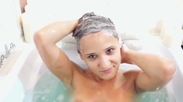 Young beautiful woman relaxing in a bath, washing herself hair and smeared nose foam