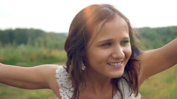 Boldogság fiatal gyönyörű barna nő emeli a karját szabadtéri napfény alatt a naplemente spinning körül, a tánc és az éneklés