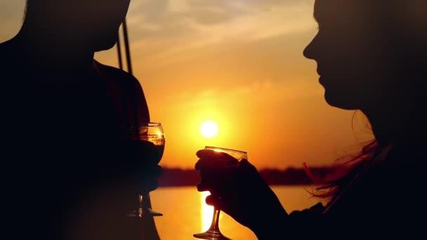 Silueta mladých šťastný pár v lásce líbání na jachtě a pít víno s brýlemi na úžasný západ slunce v slowmotion