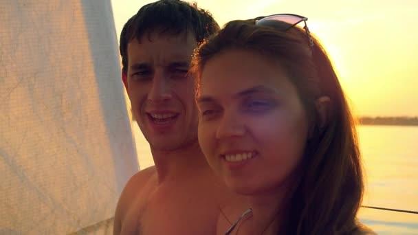 Cesta pár v lásce ve světě na jachtě. Milostný příběh. Svatební cestu na jachtě plavby při západu slunce