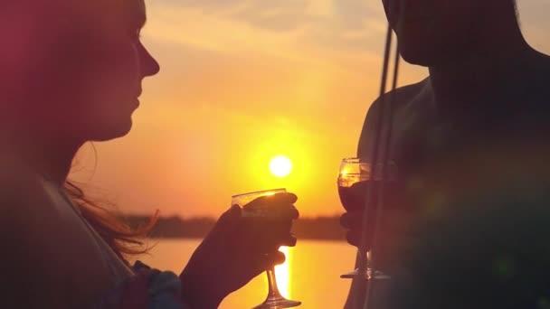 Mladý šťastný pár v lásce líbání na jachtě a pít víno s brýlemi na úžasný západ slunce v slowmotion