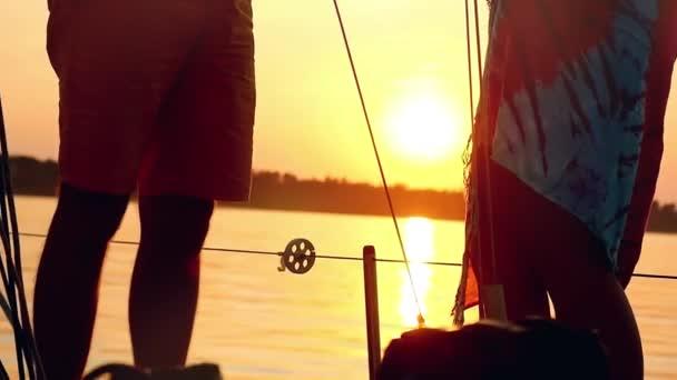 Silueta mladých šťastný pár v lásce na jachtě se sklenkami vína na úžasný západ slunce v slowmotion