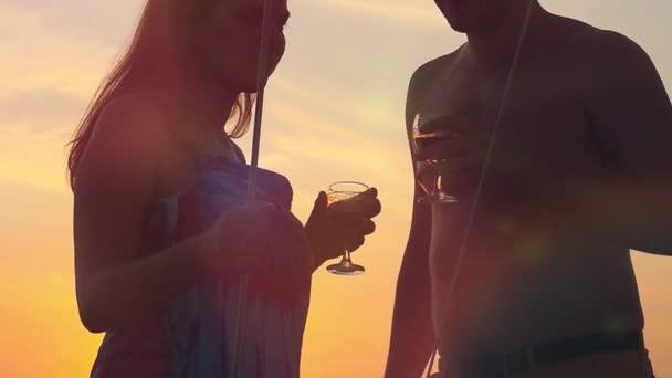 Mladý šťastný pár v lásce na jachtě se sklenkami vína na úžasný západ slunce v slowmotion