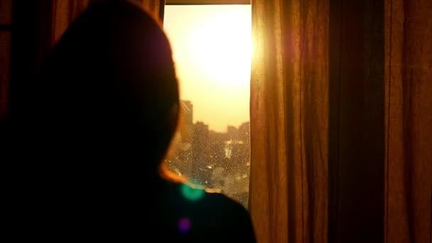 Atraktivní mladá žena otevírá záclony v pomalém pohybu se při pohledu na východ slunce stojící u okna v jejím domě a těší se z pohledu na město z výšky