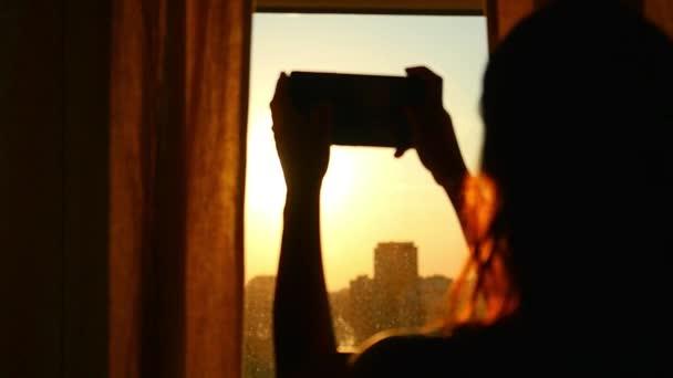 Mladé děvče brát fotografie z města s rozmazané architektury na chytrý mobil v domácí okno v pomalém pohybu