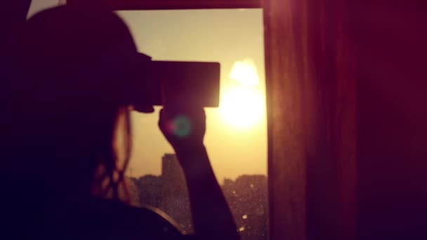 Young Girl Taking Photos Of City With blurred architectures on Mobile Smart Phone at home window in slow motion