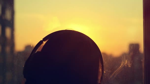 Attractive young woman listening to music on the music player at city blurred background with sunset enjoying the tunes in her headphones in slowmotion