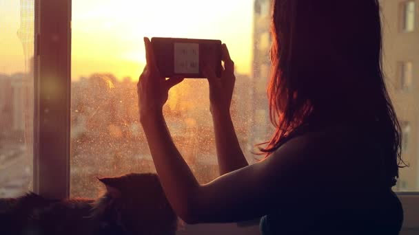 Young woman in headphones relaxing with her lovely Maine Coon cat at window taken pictures of blurred city background at sunset in slowmotion