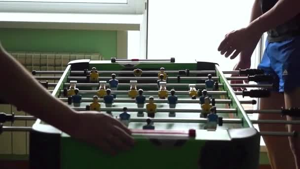 Young friends or students having fun together playing table football in slowmotion