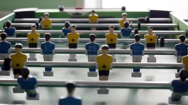 Stolní fotbal se žlutými a modrými hráči při pomalé animaci na rozostřené pozadí