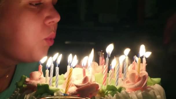 junge dicke Frau bläst Kerzen auf Geburtstagstorte bei Party