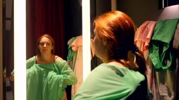 Beautiful young red-haired woman trying on dress in front of mirror in dressing room In clothing store