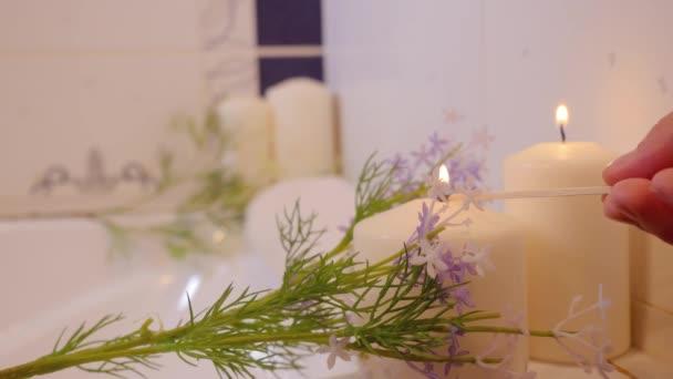 Ruka ženy hoří svíčky v koupelně. Lázně zátiší