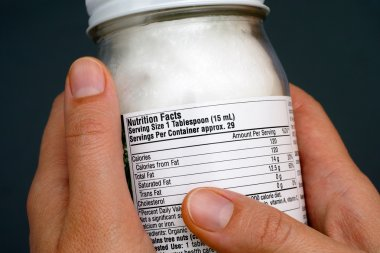 Reading a nutrition facts on coconut oil jar
