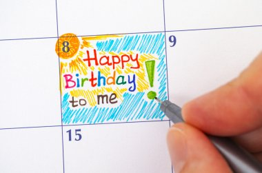 Hand with pen writing reminder Happy Birthday to me