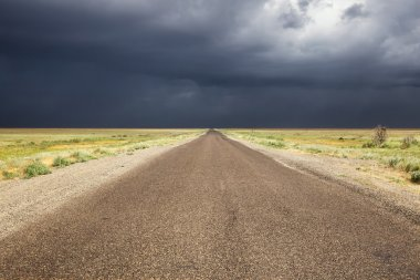 Old road in desert and storm sky