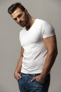Handsome young man in white t shirt and jeans on gray background