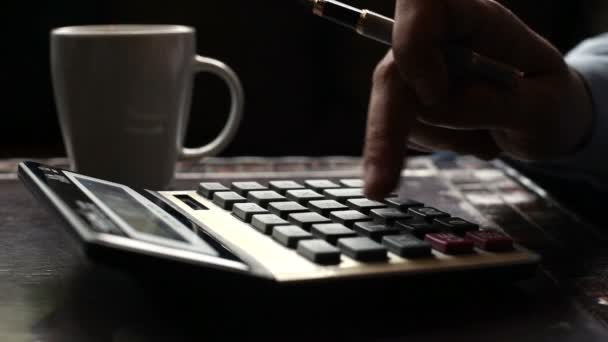 Business man typing on calculator