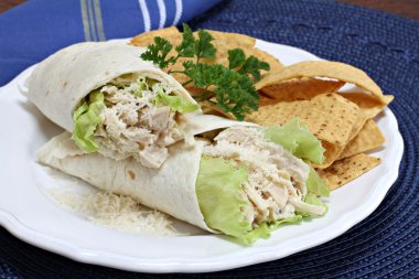Stacked chicken caesar salad sandwich wraps with a side of tortilla chips. stock vector
