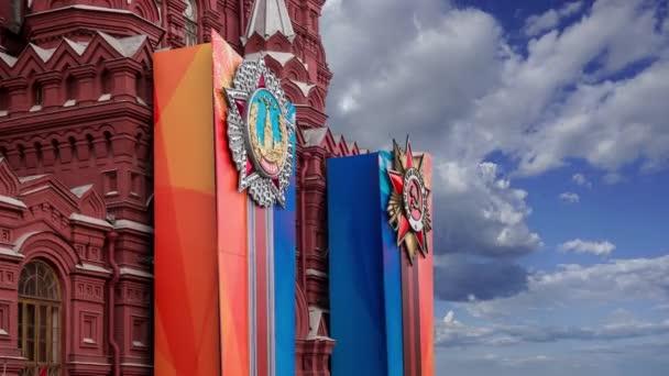 Praporce s medailemi a stuhami na fasádě historického muzea (výzdoba Dne vítězství), Rudé náměstí, Moskva, Rusko. Písemné historické muzeum a vítězství v ruštině