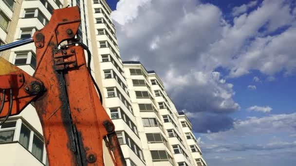 Část stavebního stroje (rypadla nebo jeřáb) s vícepodlažní budovou ve výstavbě (nový obytný komplex) na pozadí. Moskva, Rusko