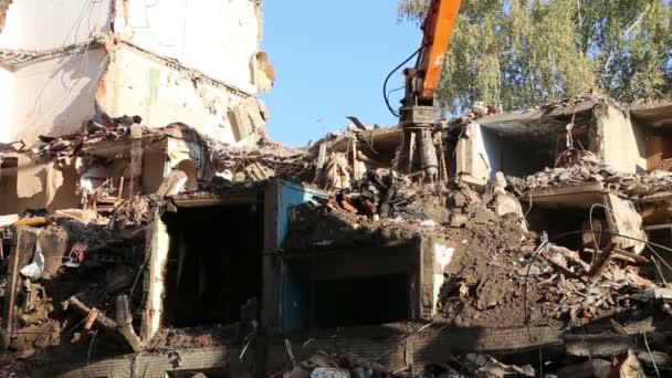 Hydraulic crusher excavator machinery working on demolition old house. Moscow,Russia