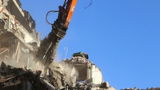 Macchinari di escavatore idraulico Frantoio lavorando sulla vecchia casa di demolizione. Mosca, Russia