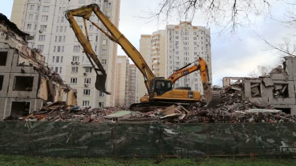 Excavator machinery working on demolition old house