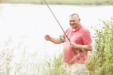 Mature angler on lake