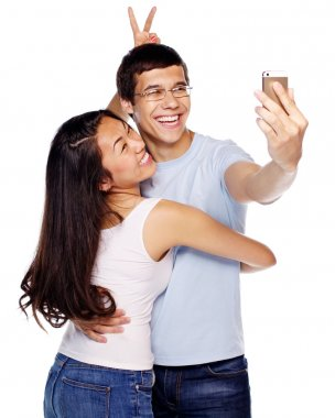 Joyful couple taking selfie with smartphone