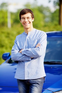 Young man leaning against car with crossed arms