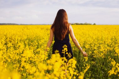 Girl enjoying rapeseed blooming on yellow meadow